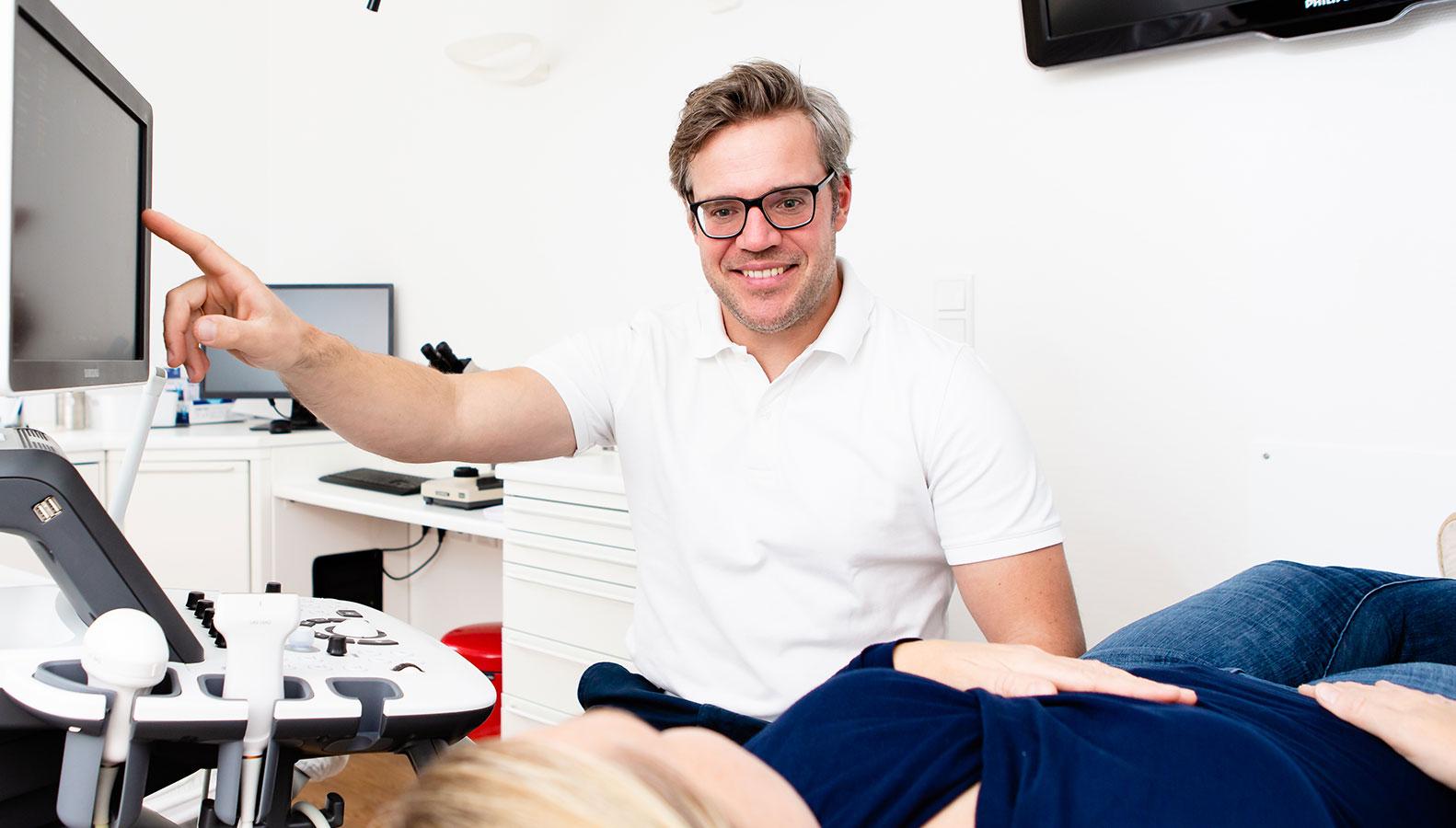 Dr. med. Moritz Kanzow erläutert einer Patientin ihr Ultraschallbild
